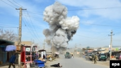 Smoke billows from the scene of a suicide bomb blast that targeted the police headquarters in the northeastern city of Kunduz in February.
