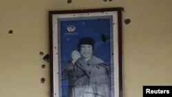 Libya -- A bullet-riddled picture of Muammar Qaddafi hangs on the wall of a cafetaria at a gas station of Bou Hadi town, 03Oct2011