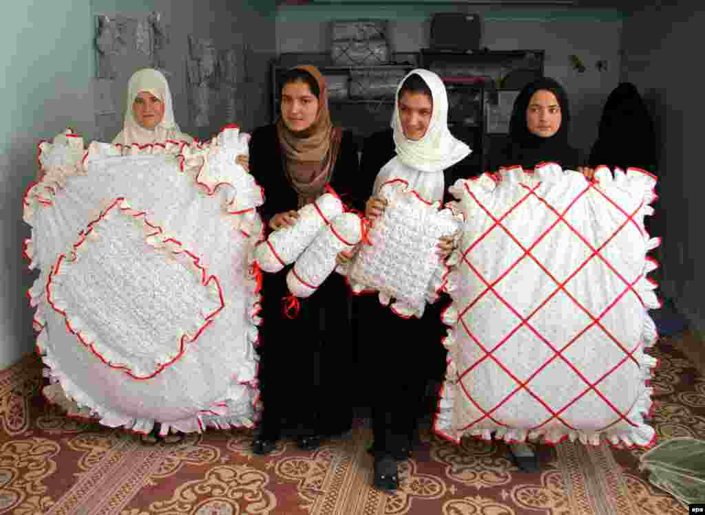 Afghan girls suffering from hearing and speech impairment display the final products after they learned to sew clothing at a center supported by the Swedish Embassy in Ghazni. (epa/Naweed Haqjoo)