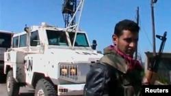 """Член """"Бригады мученников Ярмука"""" на фоне джипа с эмблемой ООН. Предположительно Джамла, Голанские высоты, 6 марта 2013 года."""