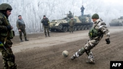 Ukrainian servicemen play football on a road at Svitlodarsk, approaching Debaltseve on February 15, hours after a cease-fire came into effect. The truce seems to have been cautiously observed by both sides, despite accusations by Kyiv and Washington that Russia had fueled a final push by rebels to gain territory before the start of the cease-fire.