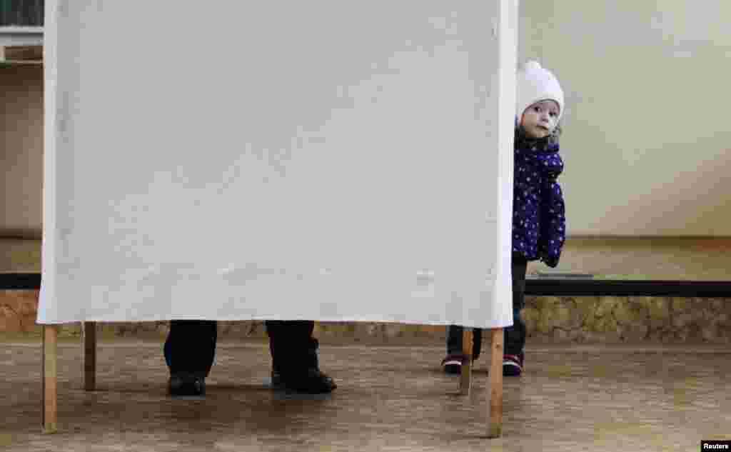 A child looks out from behind a curtain as her mother fills up her ballot.
