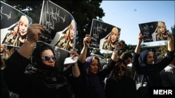Women hold pictures of Iranian poet Simin Behbahani at her funeral in Tehran on August 22.
