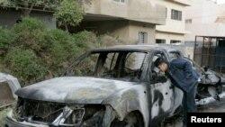 صبي يتفحّص سيارة محترقة بعد إنفجار وسط بغداد