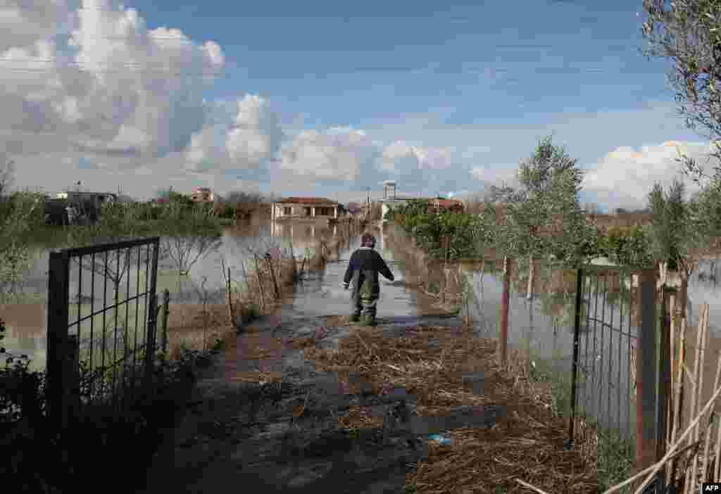 An Albanian man walks through floodwaters towards his home in the village of Mifol near the city of Vlora. (AFP/Gent Shkullaku)