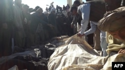 Afghan men and a woman gather around the bodies of civilians, including children, who were allegedly killed by Islamic State (IS) militants in Ghor Province on October 26.