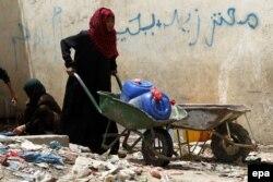 Женщина в поисках питьевой воды на улице в столице Сане. 7 апреля 2015 года