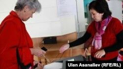 Женщины голосуют на избирательном участке в Бишкеке.
