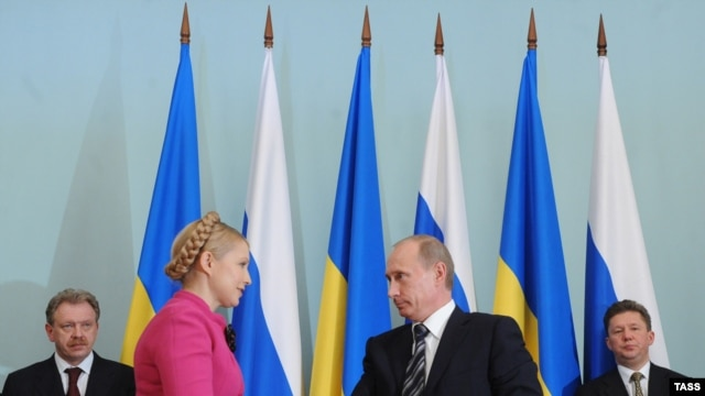 Ukraine's Yulia Tymoschenko (left) and Russia's Vladimir Putin seal the deal in Moscow.