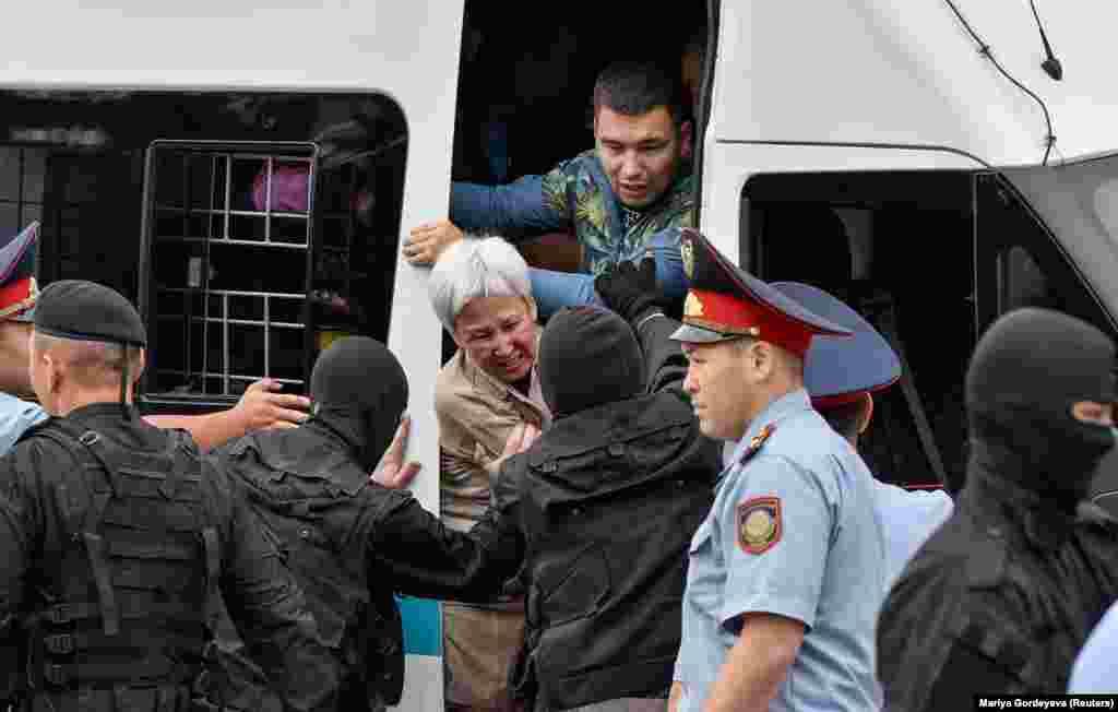 Полиция ұсталған наразыны көлікке күштеп отырғызып жатыр. Алматы, 9 маусым 2019 жыл.