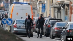 Armed Belgian police patrol near the scene of an apparent operation against terror suspects in Brussels, Belgium, on March 25.