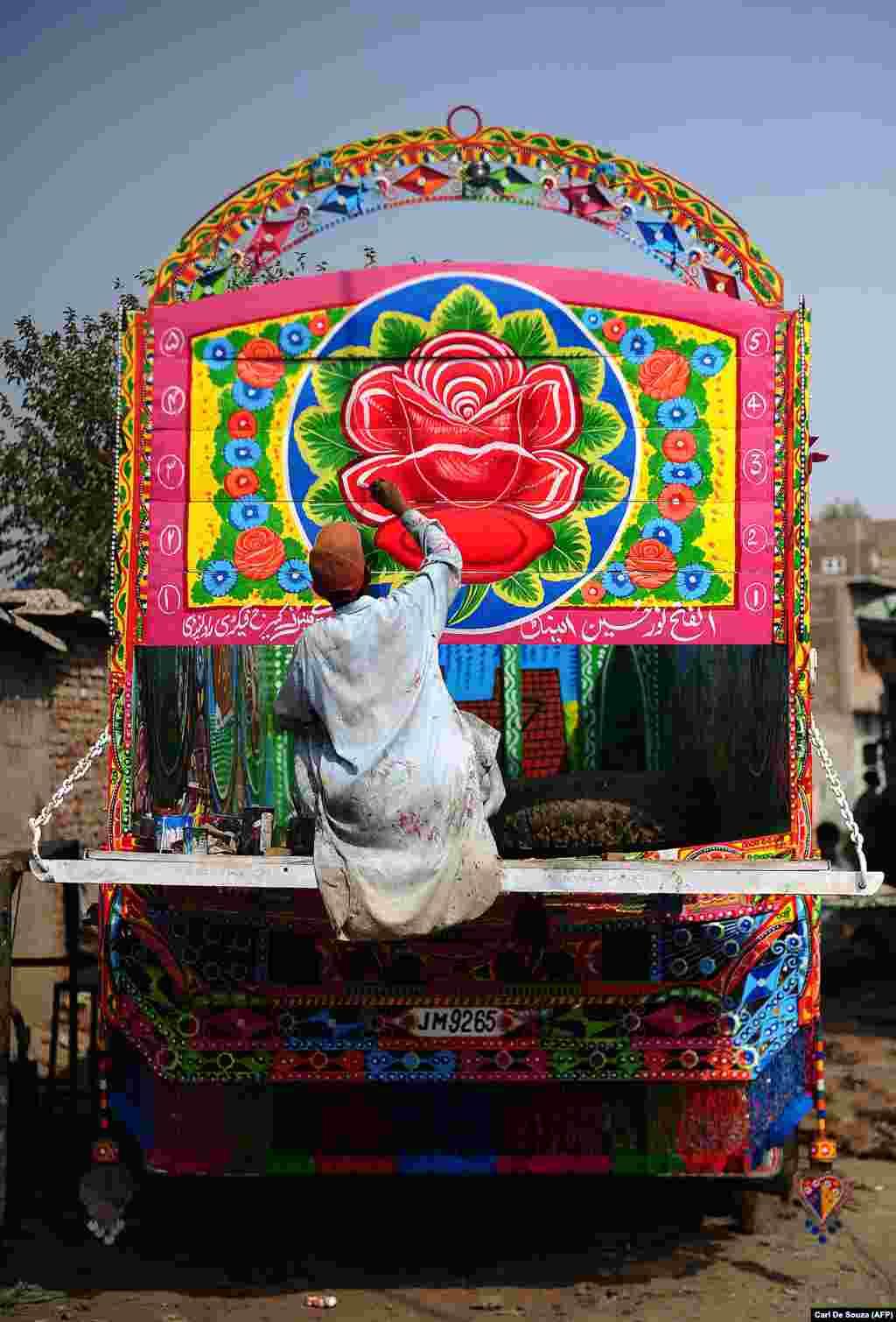 Художник по грузовикам добавляет последние штрихи к кузову грузовика в Равалпинди. Грузовики Пакистана, возможно, известны своей красочностью, но они остаются, тем не менее, средством для перевозок.