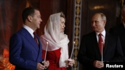 Russian President Vladimir Putin, Prime Minister Dmitry Medvedev and his wife Svetlana attend the Orthodox Easter service at the Christ the Savior Cathedral in Moscow on April 7.