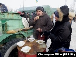 Avdiyivka residents eat and warm themselves at a humanitarian-aid station.