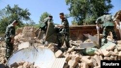Кытай -- Куткаруучулар имараттын урандыларынын арасынан адамдарды издөөдө. Диңси шаары, 22-июль, 2013.
