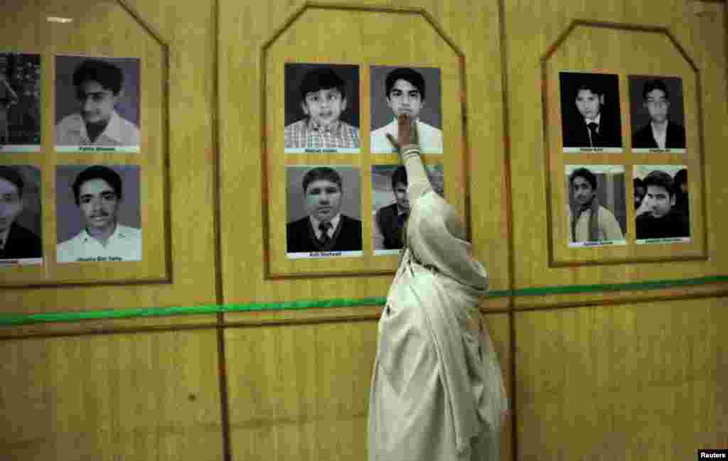 The mother of Uzair touches his picture in a gallery of the victims of the December 16, 2014, massacre by Taliban gunmen at a school in Peshawar, Pakistan. The Taliban killed 147 people in the attack, the majority of them children. (Reuters/Fayaz Aziz)
