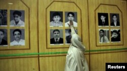 The mother of Uzair, an Army Public School victim, touches his picture in a gallery of the victims at a ceremony on the anniversary of the Taliban attack on an army school in Peshawar, December 16.