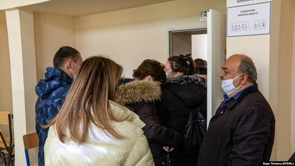 Votuesit me maska por pa mbajtur distancën presin për të votuar në një vendvotim në Mitrovicën Veriore.