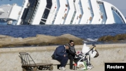 "A couple feed their child while sitting on a dock in front of the ""Costa Concordia"" cruise ship that ran aground off the Italian island of Giglio on January 15."