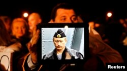 Кипрде жашаган орусиялык киши парламентке нааразылык билдирген акцияда орус президенти Путиндин сүрөтүн кармап турат. 22-март, 2013.