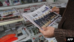 An Iranian man looks at newspapers displayed outside a kiosk in the capital Tehran on November 25, a day after an extension to talks on the country's nuclear program was announced in Vienna.