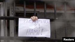 """Задержанный в Минске участник акций протеста держит в руках лист бумаги со словами:""""Победа за нами"""""""
