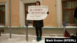 Участница акции памяти активиста партии «Другая Россия» Александра Долматова с плакатом.