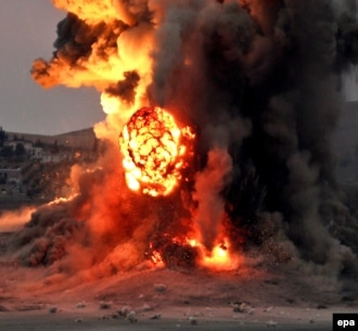 Syria -- An explosion is seen after an apparent airstrike carried out by the international anti-Islamic State (IS) coalition as part of operation Inherent Resolve on the Syrian town of Kobani, October 23, 2014