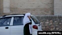 Uzbekistan - an Uzbek woman talking on a mobile passing from Uzbek car Matiz, undated