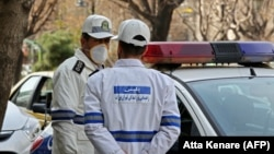 Iran -- Emergency first responders wearing protective masks stand along a street in Tehran, February 24, 2020