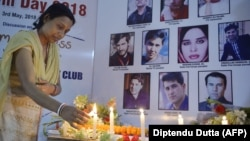 An Indian journalist lights candles during a vigil for Afghan journalists who were killed in a targeted suicide bombing in April, including two reporters who worked for RFE/RL's Radio Free Aghanistan, as well as a female trainee.