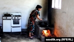 Uzbekistan - because of the lack of the gas Uzbek woman is using wood to cook a food, undated