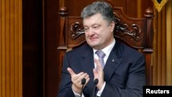 Ukrainian President Petro Poroshenko applauds during a session of parliament in Kyiv on June 19, during which deputies endorsed his nominations for key government posts.