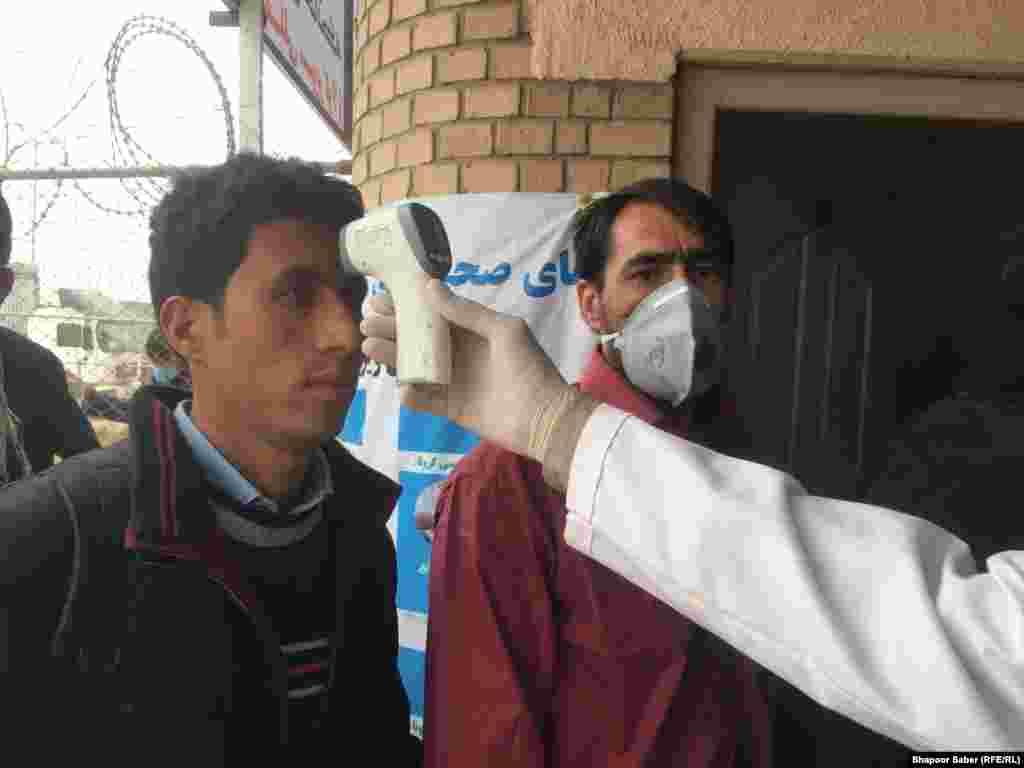 کارکن صحی در مرز اسلام قلعه درجه تب افغانی را که از ایران برگشته معاینه میکند.