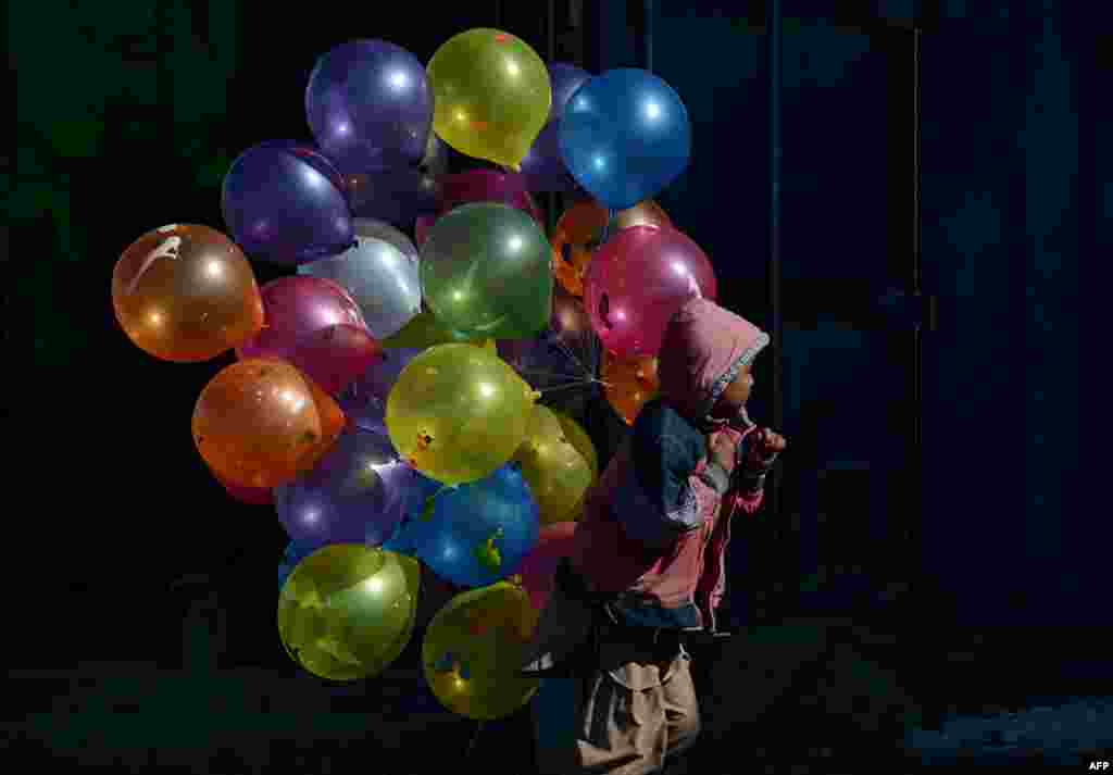 An Afghan boy walks with balloons for sale on a cold winter's day in Kabul. (AFP/Shah Marai)