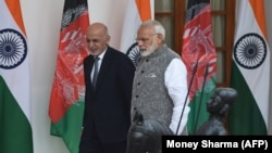 Indian Prime Minister Narendra Modi (R) and Afghan President Mohammad Ashraf Ghani walk together before a meeting in New Delhi on October 24.