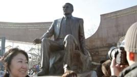 Люди у монумента в парке первого президента. Алматы, 11 ноября 2011 года.