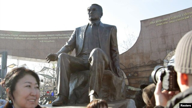 People attend a ceremony to unveil a monument that includes a sculpture of President Nursultan Nazarbaev in Almaty on November 11.