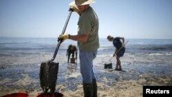 Voluntari curăță de petrol o plajă din California
