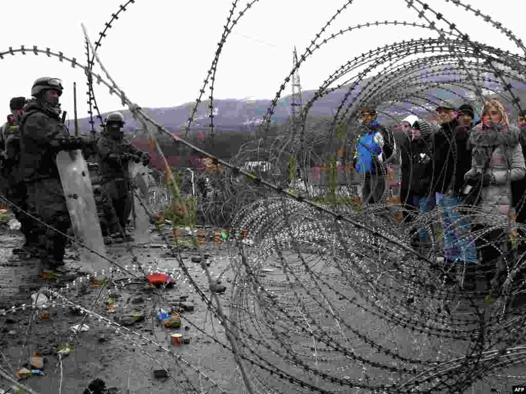 Ethnic Serbs stand by a barbed-wire barricade erected by KFOR soldiers at a roadblock near the village of Jagnjenica in northern Kosovo on December 6 (Photo for AFP by Sasa Djordjevic)