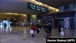 Темір жол вокзалының алдында такси күтіп тұрған адамдар. Ухань, Қытай, 23 қаңтар 2020 жыл.