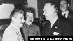 Германия сыртқы істер министрі Риббентроп (оң жақтан екінші) пен Сталин (сол жақ шетте) қол алысып тұр.