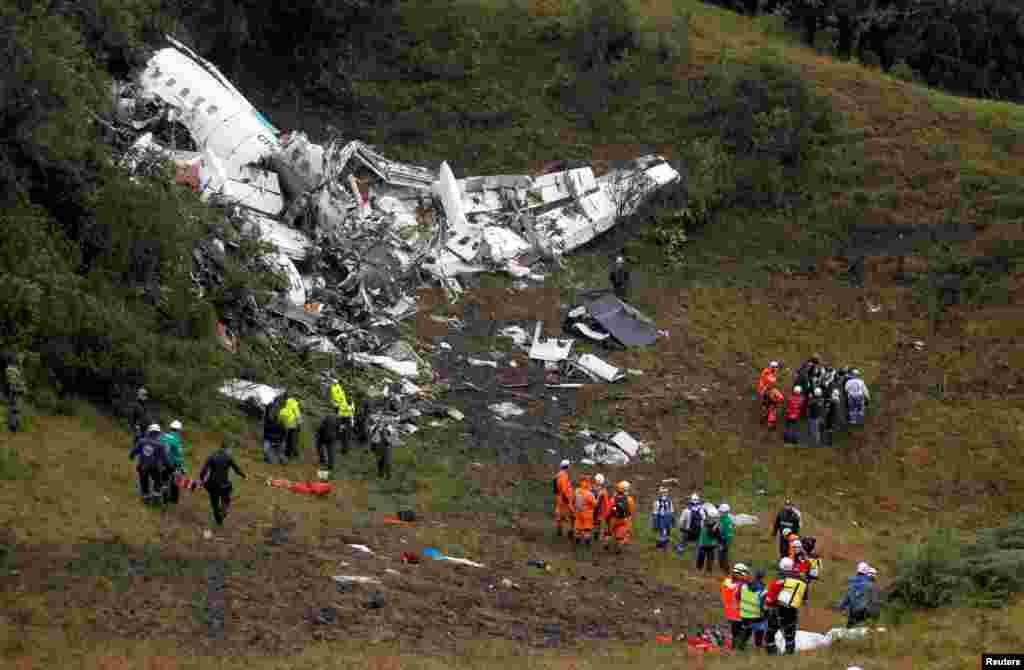 """მაშველთა ჯგუფი კოლუმბიის ჯუნგლებში ჩამოვარდნილი თვითმფრინავის ნამსხვრევებთან. თვითმფრინავით მგზავრობდა ბრაზილიის საფეხბურთო გუნდი """"ჩაპეკოენსე"""". ავიაკატასტროფის შედეად 76 ადამიანი დაიღუპა."""
