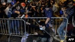 نیروهای پلیس در حال پاشیدن گاز فلفل به یکی از معترضان