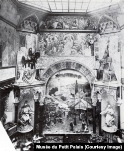 The interior of the Bosnian pavilion after it opened to the public. Beneath the archway, a painting of a Sarajevo marketplace rises above some carpets.