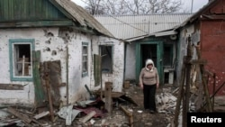 A woman walks out of her damaged house in the town of Debaltseve, northeast of Donetsk, on March 17.
