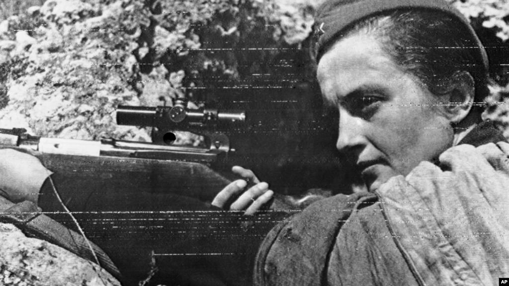 Зображена на фото українка Людмила Павличенко – найуспішніша в історії жінка-снайпер. Вона захищала Одесу і Севастополь, була евакуйована і вирушила з делегацією молоді в США і Канаду.  Переконуючи союзників відкрити фронт у Європі, вона сказала: «Мені 25 років, на фронті я встигла знищити 309 фашистських загарбників. Чи не здається вам, джентльмени, що ви занадто довго ховаєтеся за моєю спиною?».  За різними даними, майже третина захисників Севастополя були українцями