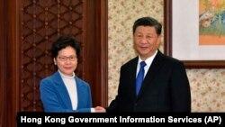 ჰონგ-კონგის ხელისუფლების მეთაური კერი ლამი (მარცხნივ) და ჩინეთის პრეზიდენტი სი ძინპინი. 2019 წ. დეკემბრის ფოტო.