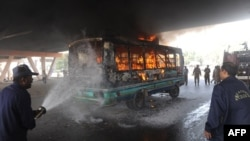 Firefighters extinguish a fire after protesters set alight a passenger bus in Karachi on March 27.