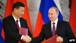 Russian President Vladimir Putin (right) and his Chinese counterpart, Xi Jinping, shake hands during a signing ceremony in the Kremlin in Moscow on July 4.